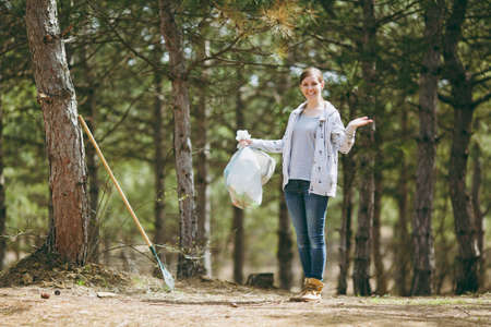 Young smiling woman cleaning rubbish holding trash bags and spreading hands in park on green background. Problem of environmental pollution. Stop nature garbage, environment protection concept