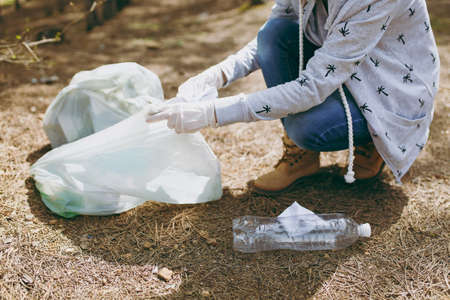 Cropped Young woman in casual clothes, gloves cleaning rubbish into trash bags in park on green background. Problem of environmental pollution. Stop nature garbage, environment protection concept