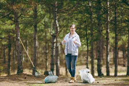 Young smiling woman in casual clothes cleaning rubbish showing thumbs up in park or forest on green background. Problem of environmental pollution. Stop nature garbage, environment protection concept Stockfoto