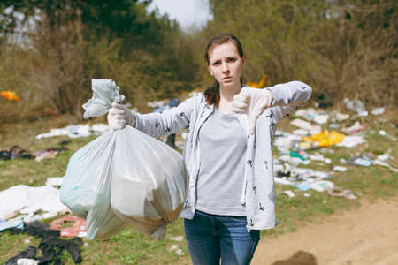 Young upset woman in casual clothes cleaning holding trash bags and showing thumb down in littered park. Problem of environmental pollution. Stop nature garbage, environment protection concept Standard-Bild