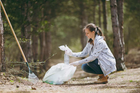 Young woman in casual clothes, gloves cleaning rubbish into trash bags in park or forest on green background. Problem of environmental pollution. Stop nature garbage, environment protection concept Standard-Bild