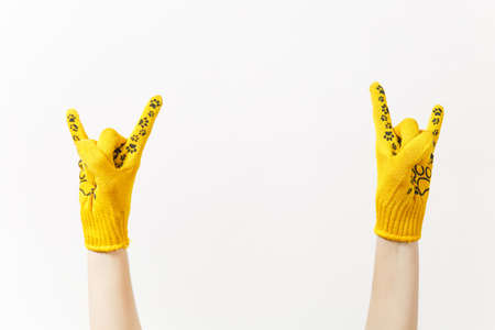 Close up of female hands in building yellow gloves horns gesture, depicting heavy metal rock and roll sign isolated on white background. Accessories for renovation apartment room. Advertising area Stock Photo