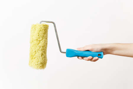 Close up of female hand horizontal holds paint roller for wall painting isolated on white background. Instruments for renovation apartment room. Repair home concept. Copy space for advertisement