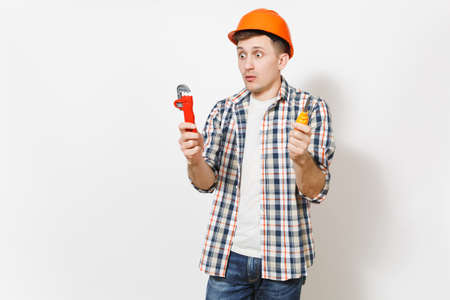 Young shocked handsome man in protective orange hardhat holding toy screwdriver and adjustable wrench isolated on white background. Instruments for renovation apartment room. Repair home concept 写真素材
