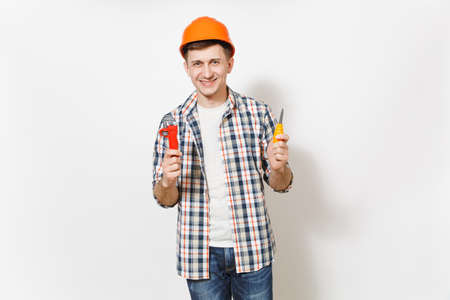 Young smiling handsome man in protective orange hardhat holding toy screwdriver and adjustable wrench isolated on white background. Instruments for renovation apartment room. Repair home concept 写真素材