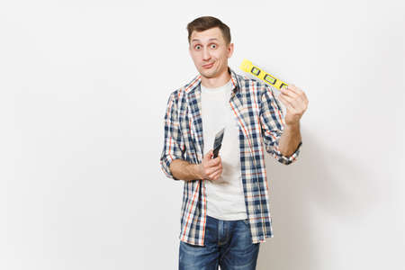 Young concerned handsome man in casual clothes holding putty knife and building bubble spirit level isolated on white background. Instruments for renovation apartment room. Repair home concept