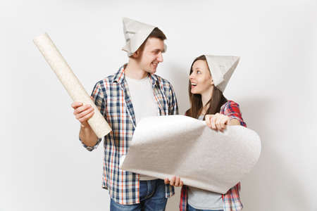 Young happy woman, man in casual clothes and newspaper hats holding wallpaper rolls. Couple isolated on white background. Instruments, accessories for renovation apartment room. Repair home concept
