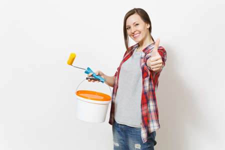 Smiling woman holding empty paint bucket with copy space and paint roller and showing thumb up on camera isolated on white background. Instruments for renovation apartment room. Repair home concept
