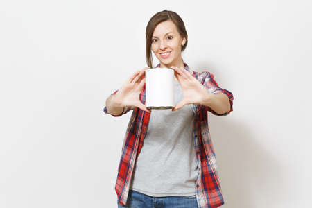 Young smiling beautiful woman pointing empty paint tin can with copy space on camera isolated on white background. Instruments, accessories, tools for renovation apartment room. Repair home concept
