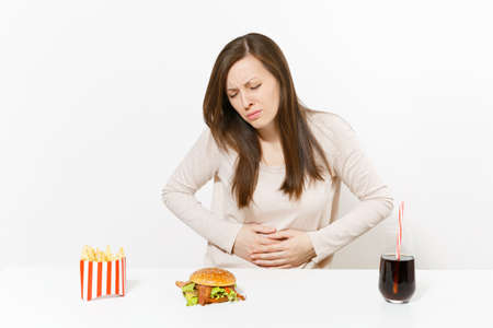 Illness woman put hands on pain abdomen, stomach-ache at table with burger, french fries, cola in glass bottle isolated on white background. Proper nutrition or American classic fast food. Copy space Stockfoto