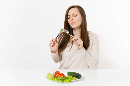 Vegan woman at table with leaves salad lettuce, vegetables on plate isolated on white background. Proper nutrition, vegetarian food, healthy lifestyle dieting concept. Advertising area to copy space