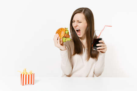 Angry screaming woman sitting at table with burger, french fries, cola in glass bottle isolated on white background. Proper nutrition or American classic fast food. Advertising area with copy space Banco de Imagens - 102232233