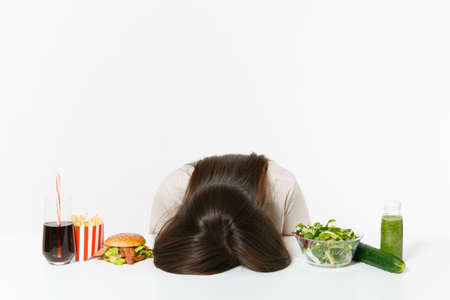 Woman put head on table with green detox smoothies, salad in glass bowl, cucumber, burger, cola in bottle isolated on white background. Proper nutrition, healthy lifestyle, fast food, dieting concept