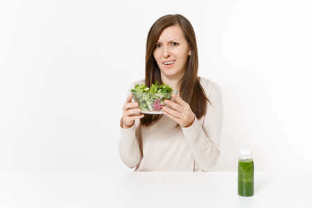 Dissatisfied woman at table with green detox smoothies, salad in glass bowl isolated on white background. Proper nutrition, vegetarian food, healthy lifestyle, dieting concept. Area with copy space