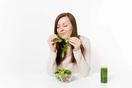 Woman sitting at table with green detox smoothies, salad in glass bowl, hands isolated on white background. Banque d'images
