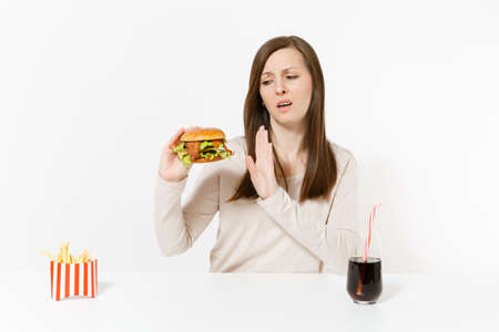 Severe woman shows stop gesture at table with burger french fries cola in glass bottle isolated on white background. Proper nutrition or American classic fast food. Advertising area with copy space