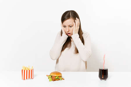 Shocked woman put hands on head at table with burger french fries cola in glass bottle isolated on white background. Proper nutrition or American classic fast food. Advertising area with copy space