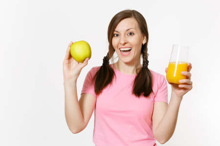 Beautiful fun happy woman holding in hands green apple and orange fresh juice in glass isolated on white background. Proper nutrition, dieting concept. Copy space for advertisement. Advertising area