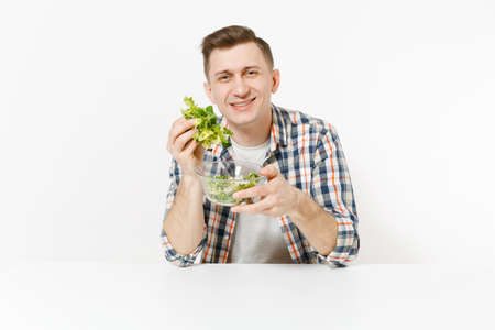 Young man sitting at table with green fresh salad in glass bowl isolated on white background. Proper nutrition, vegetarian food, healthy lifestyle, dieting concept. Advertising area with copy space