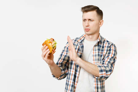 Severe young man holding burger, showing stop gesture with palm isolated on white background. Proper nutrition or American classic fast food. Motivation, choice concept. Advertising area copy space