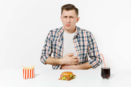 Illness man put hands on pain abdomen, stomach-ache at table with burger, french fries, cola in glass isolated on white background. Proper nutrition or American classic fast food Area with copy space