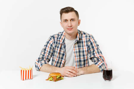 Handsome young man in shirt sitting at table with burger, french fries, cola in glass isolated on white background. Proper nutrition or American classic fast food. Advertising area to copy space 写真素材