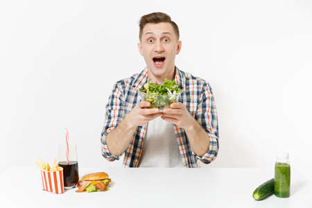 Man sits at table with green detox smoothies, salad in glass bowl, cucumber, burger, fries, cola in glass isolated on white background. Proper nutrition, healthy lifestyle, fast food, choice concept