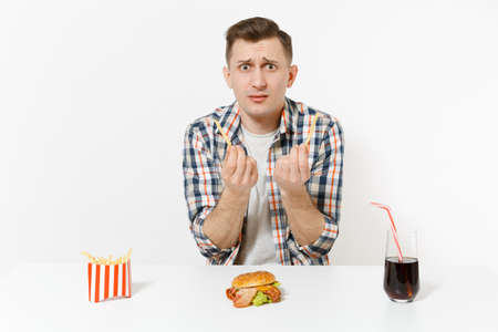 Handsome young man in shirt sitting at table with burger, french fries, cola in glass isolated on white background. Proper nutrition or American classic fast food. Advertising area with copy space. 写真素材