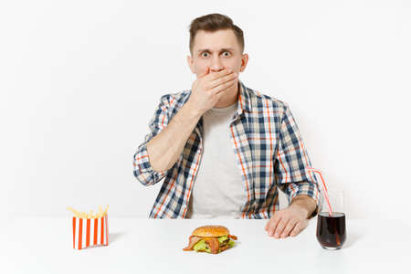 Handsome young man sitting at table with burger, french fries, cola in glass isolated on white background. Proper nutrition or American classic fast food. Advertising area with copy space.