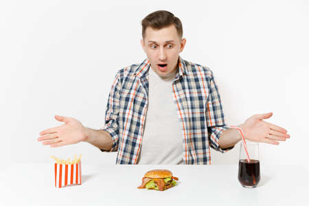 Shocked young man spreading hands, sitting at table with burger, french fries, cola in glass isolated on white background.