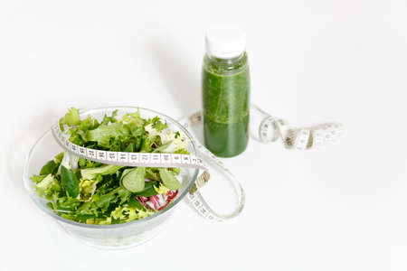 Green detox smoothies, vegetables salad in glass bowl, tailor measuring tape isolated on white background.
