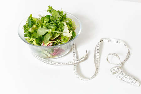 Close up green vegetables salad in glass bowl, tailor measuring tape isolated on white background.