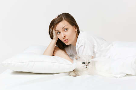 Calm young woman lying in bed with white cute Persian silver chinchilla cat, sheet, pillow, blanket on white background. Beauty female spending time in room. Rest, relax good mood concept. Copy space
