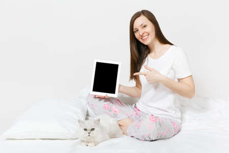 Woman sitting in bed with white cute Persian silver chinchilla cat isolated on white background. Female with tablet pc computer with blank screen spending time in room. Rest, relax, good mood concept
