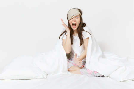 Fun tired young woman sitting in bed with sleep mask, sheet, pillow, wrapping in blanket isolated on white background. Beauty female spending time in room. Rest, relax, good mood concept. Copy space Stock fotó