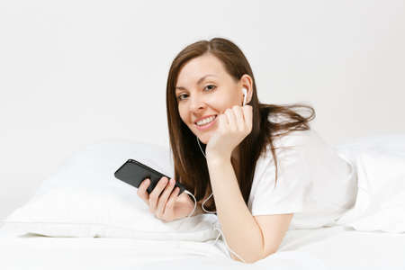 Calm young woman lying in bed with white sheet, pillow, blanket on white background. Beauty female listening music from earphones in mobile phone, spending time in room. Rest, relax good mood concept