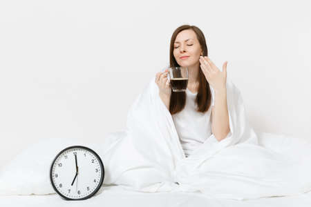 Happy woman sitting in bed with round clock, white sheet, pillow, wrapping in blanket on white background. Beauty female wake up early in morning, enjoys aroma of coffee. Rest relax good mood concept