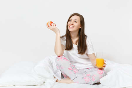 Young brunette woman sits on bed with white sheet, pillow, wrapping in blanket isolated on white background. Beauty female have breakfast with apple, fresh orange juice. Rest, good mood concept
