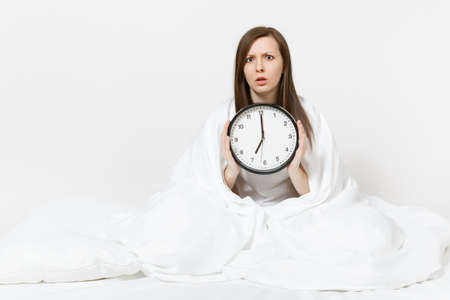 Young woman sitting in bed with round clock, white sheet, pillow, wrapping in blanket on white background. Beauty female wake up early in morning, spending time in room. Rest, good mood concept