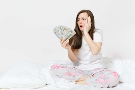Young screaming sad woman sitting in bed with white sheet, pillow, wrapping in blanket on white background. Beauty female holding bundle of dollars, cash money in room. Rest, relax, good mood concept