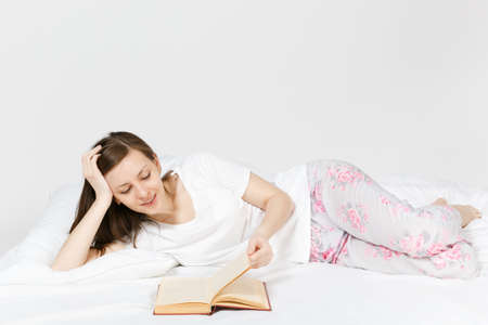 Young happy woman lying in bed with white sheet, pillow, blanket on white background. Beauty female spending time in room, reading book, enjoying of rest. Relax, good mood concept. Place for text