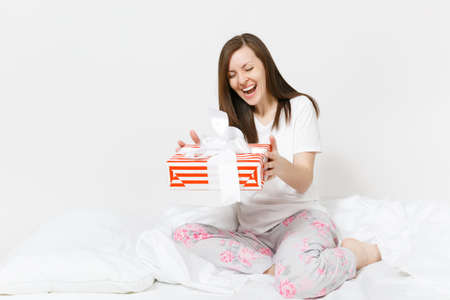 Young brunette woman sitting in bed with red striped gift box, white sheet, pillow, wrapping in blanket isolated on white background. Beauty female spending time in room. Rest relax good mood concept