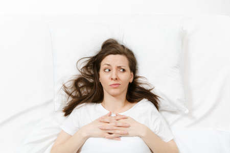 Top view of tired stressed crying young woman lying in bed with white sheet, pillow, blanket. Pensive frustrated sad upset female spending time in room. Rest, relax, bad mood concept. Copy space Stock Photo