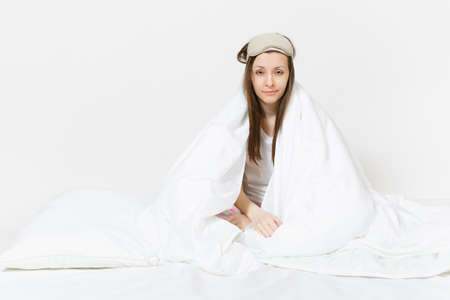 Fun tired young woman sitting in bed with sleep mask, sheet, pillow, wrapping in blanket isolated on white background. Beauty female spending time in room. Rest, relax, good mood concept. Copy space Stock Photo