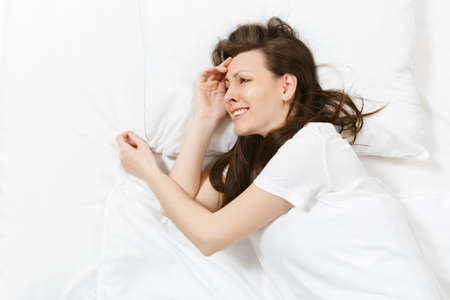 Top view of tired stressed crying young brunette woman lying in bed with white sheet, pillow, blanket. Shocked frustrated sad upset female lies on her side. Rest, relax, bad mood concept. Copy space
