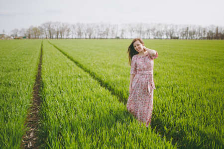 Young brunette smiling relaxed beautiful woman in light patterned dress keeping hand near neck walking in sunny weather in field on green background.