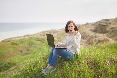 Young irritated dissatisfied business woman or student in casual clothes sitting on grass using laptop in field spreading hands working outdoors on green background.