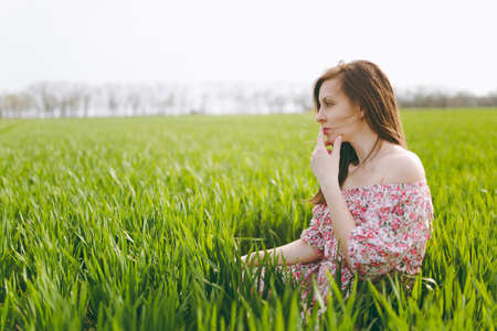 Young pensive beautiful woman in light patterned dress sitting on grass keeping hand near mouth resting in sunny weather in field on bright green background. Imagens