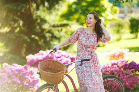 Portrait of trendy young woman in long pink floral dress stop to riding on vintage bike with basket for purchases, flowers background outdoors. Pretty female recreation time in spring or summer park