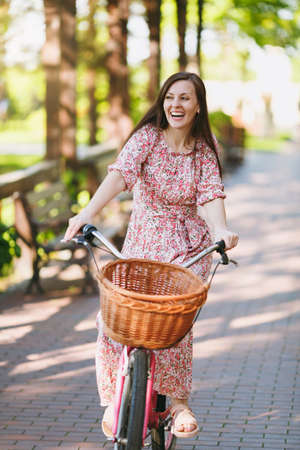 Portrait of trendy young woman in long pink floral dress riding on alley on vintage bike with basket for purchases, food or flowers outdoors, gorgeous female recreation time in spring or summer park